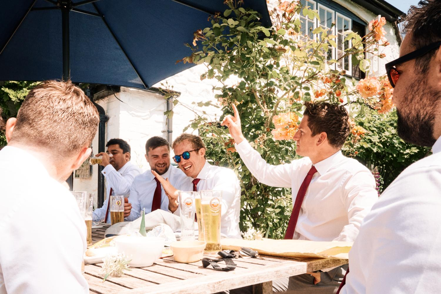 Groom and friends drink and laugh in the sun