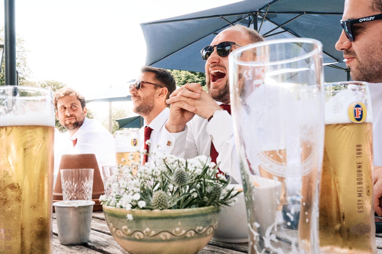Groomsmen laughing and drinking beer
