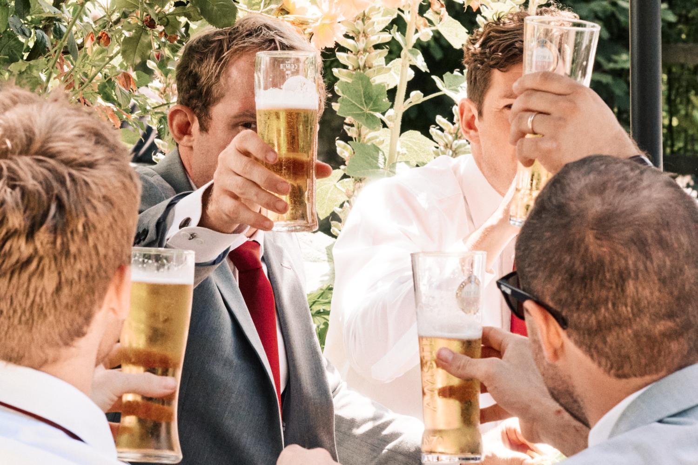 Groomsmen lift pints of beer in the air