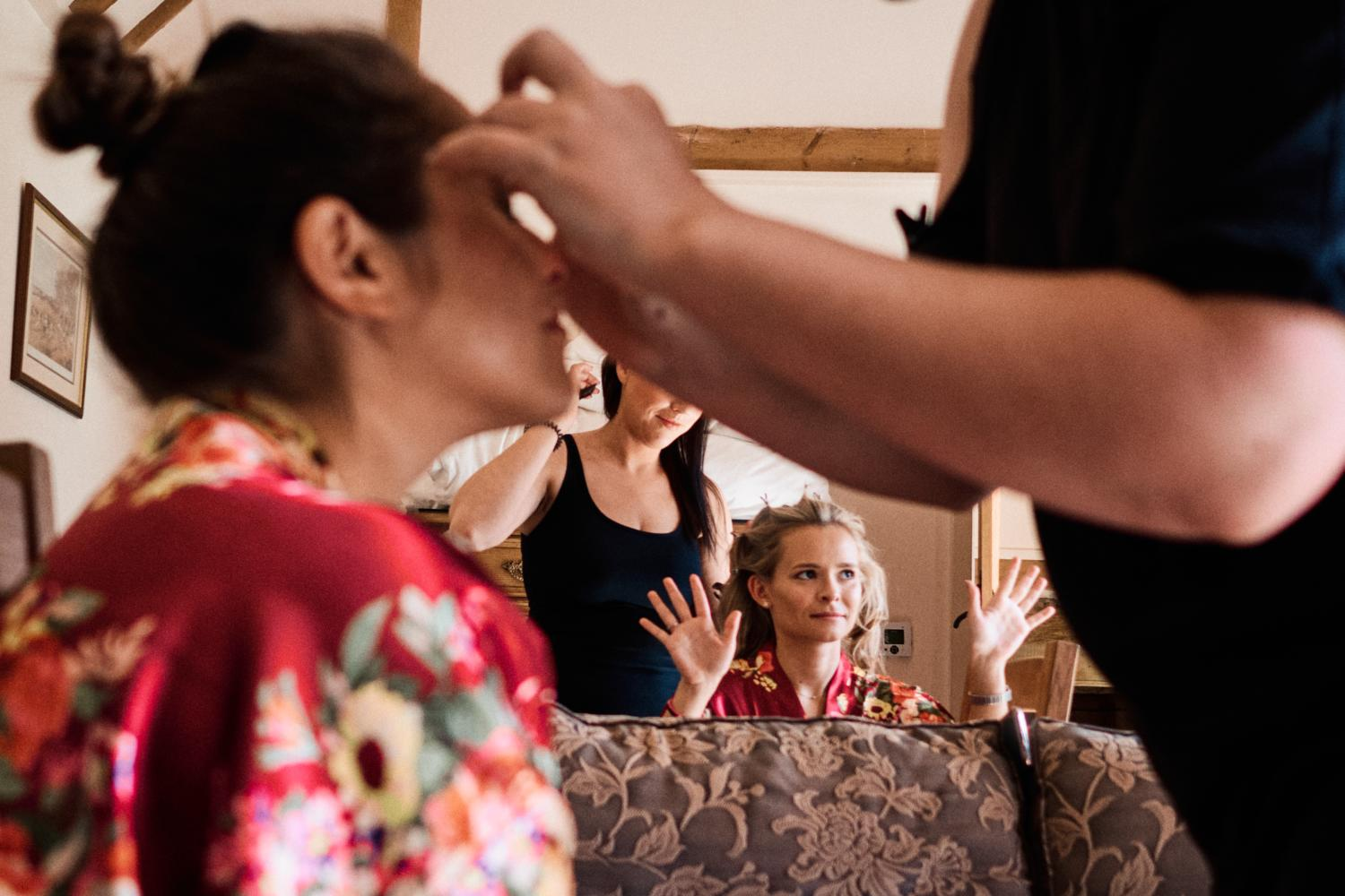 A bridesmaid raises her hands in celebration as another has her makeup applied