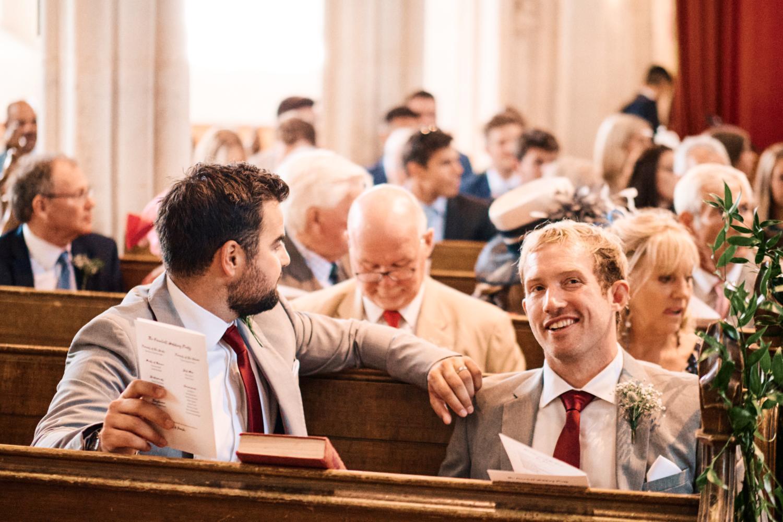 A groom smiles in a church