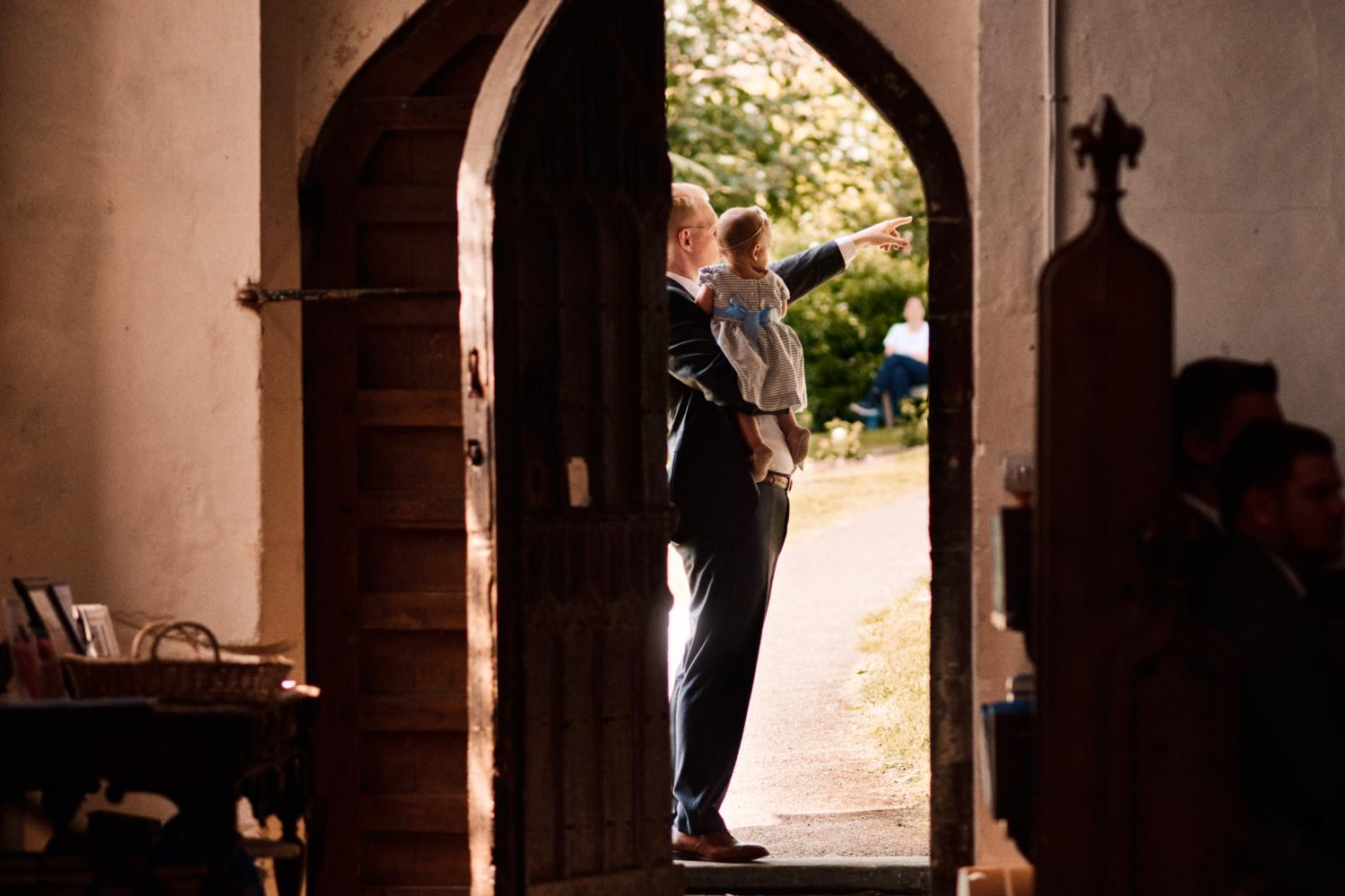A father points to something outside a church