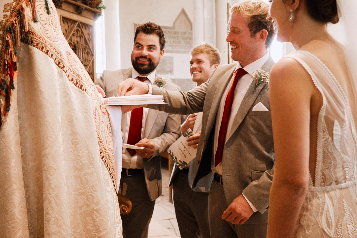 A groom reaches for rings during the vows
