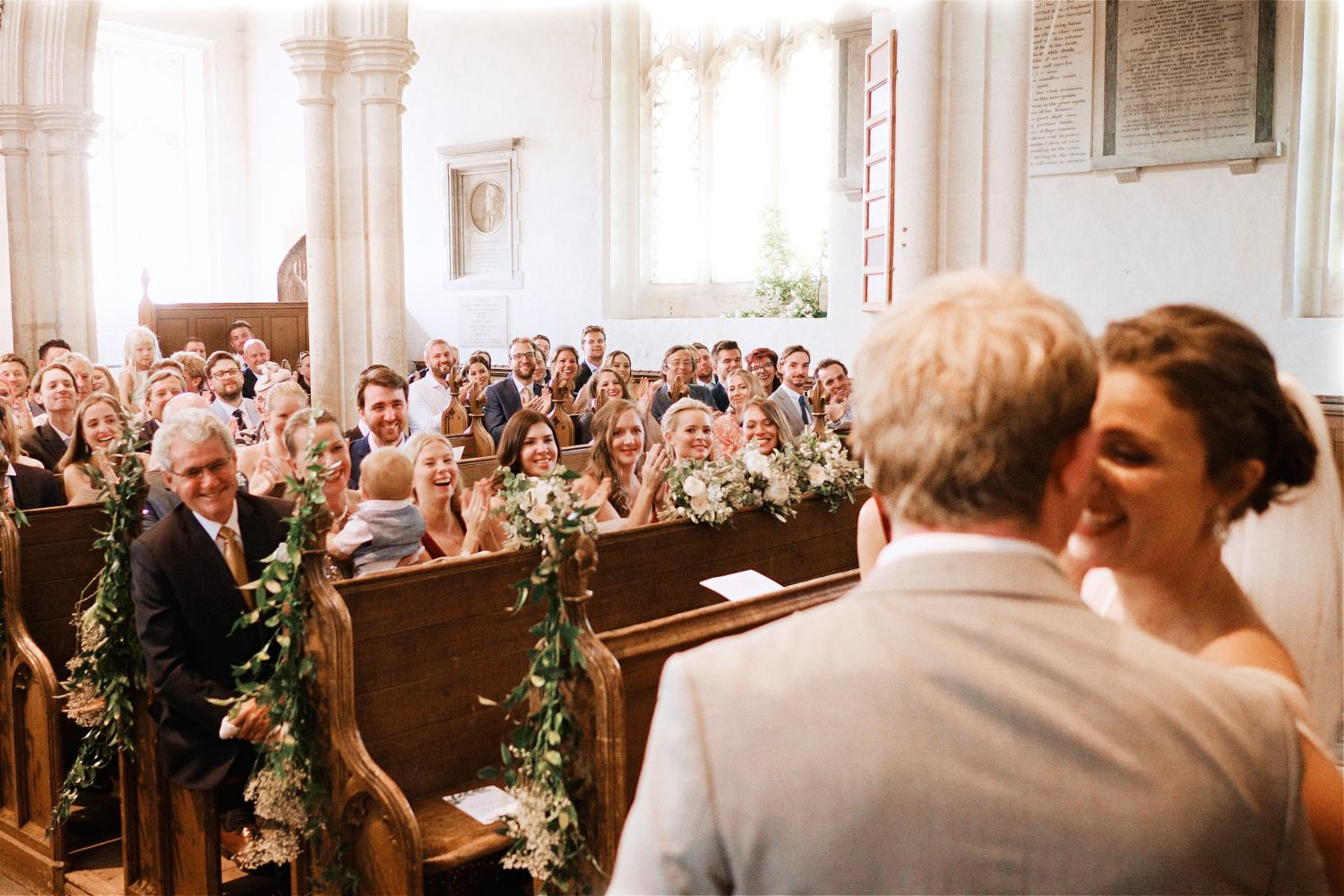Guests cheer a newly wedded couple in a church