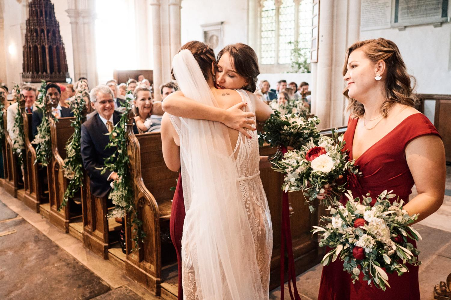A bride affectionarely hugs her sister during a wedding ceremony in Ewelme, England