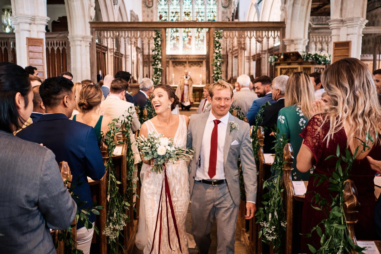 Bride and groom walk down the aisle at Ewelme Church