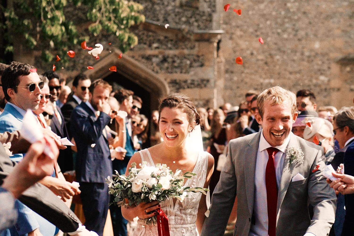 Guests throw confetti at bride and groom outside Ewelme Church