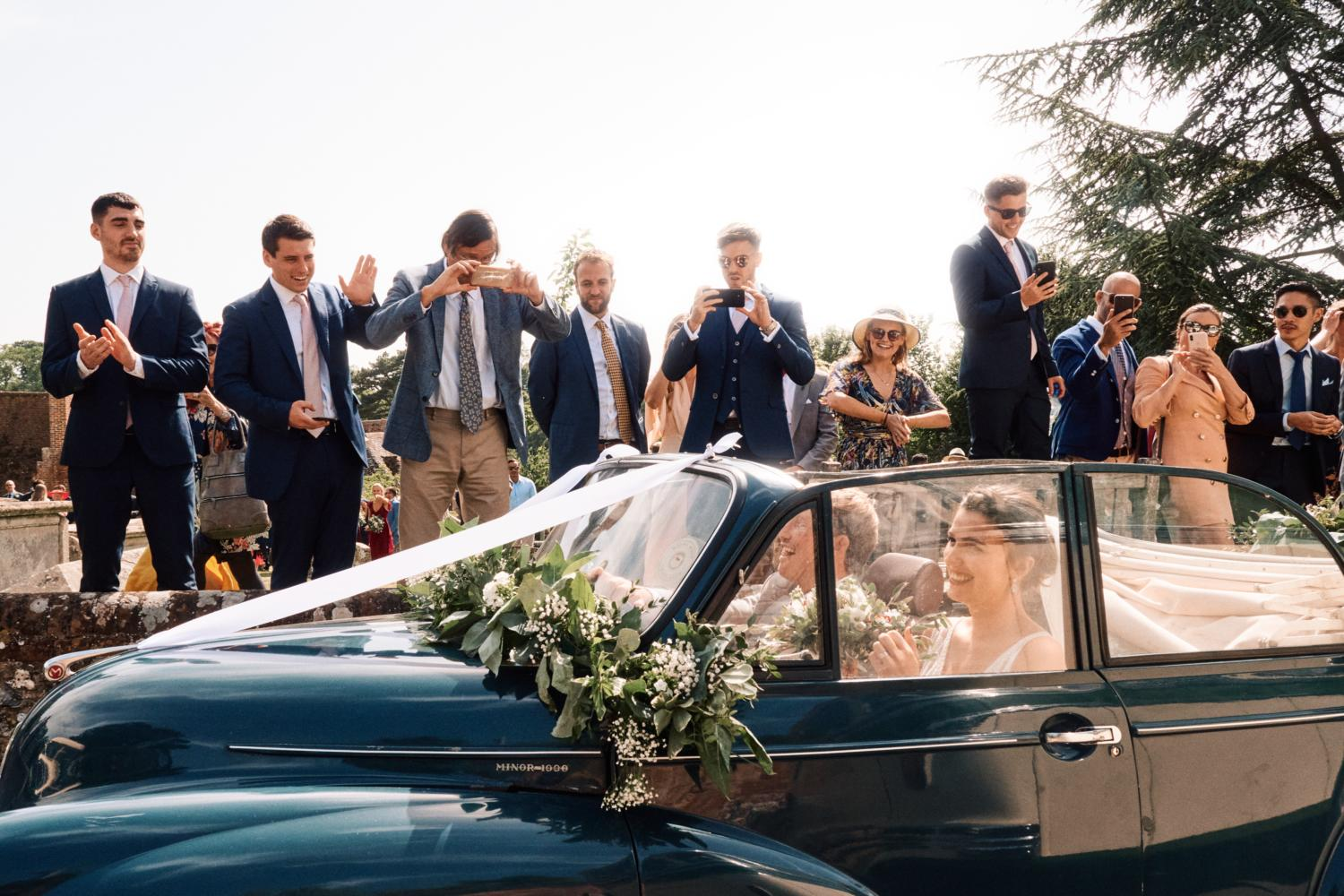 Bride and groom drive away from church in a blue convertible car