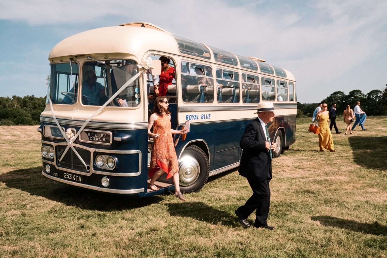 Wedding guests arrive on a blue Vintage bus