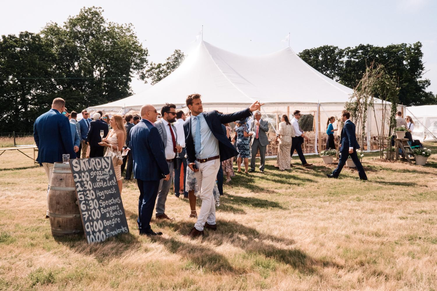 Guests mingle outside a marquee in a field