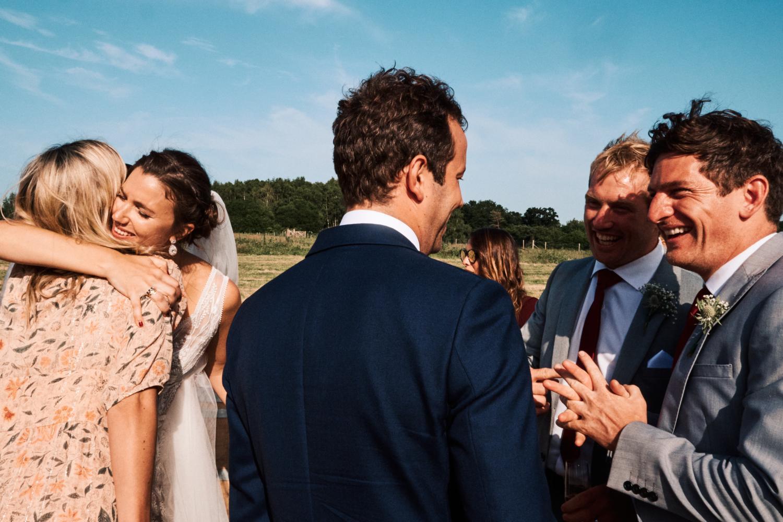 A bride hugs a friend at an outdoor wedding reception in Ewelme