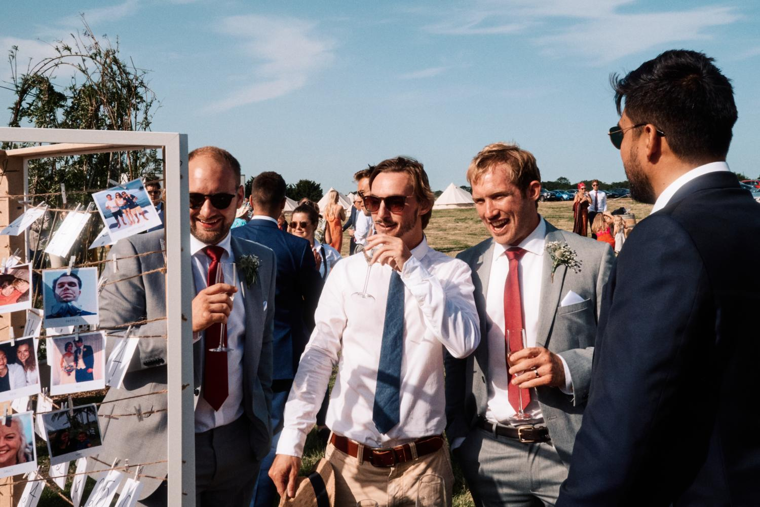 Groomsmen laugh and enjoy drinks at an outdoor wedding reception