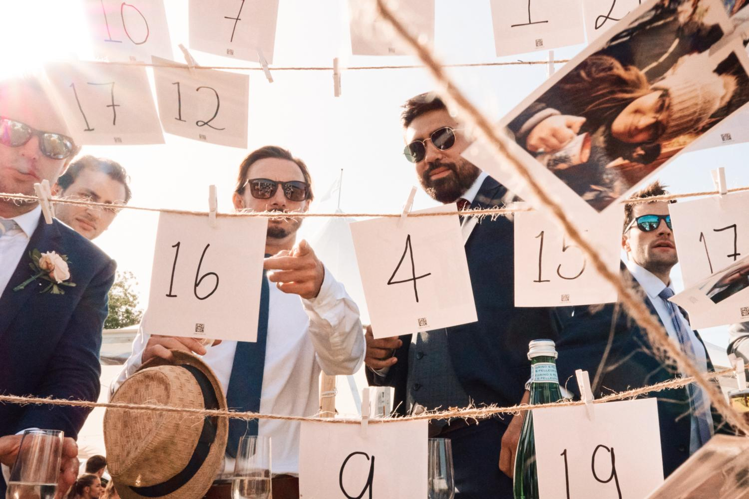 Men in sunglasses look at a picture display with numbers