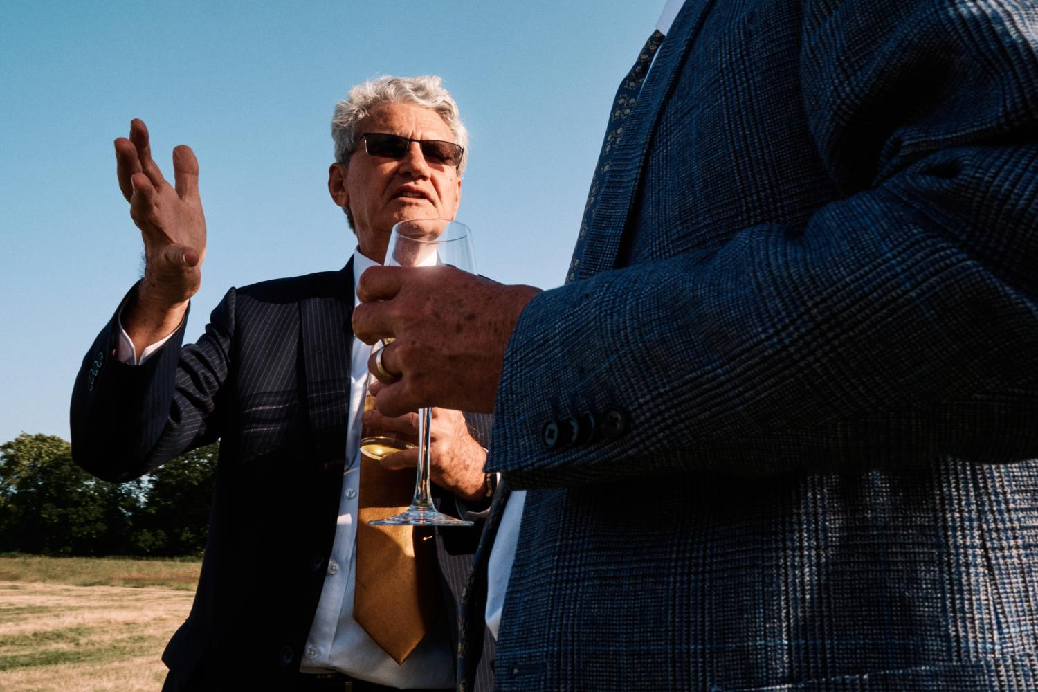 A man in sunglasses gestures to a friend with his hand