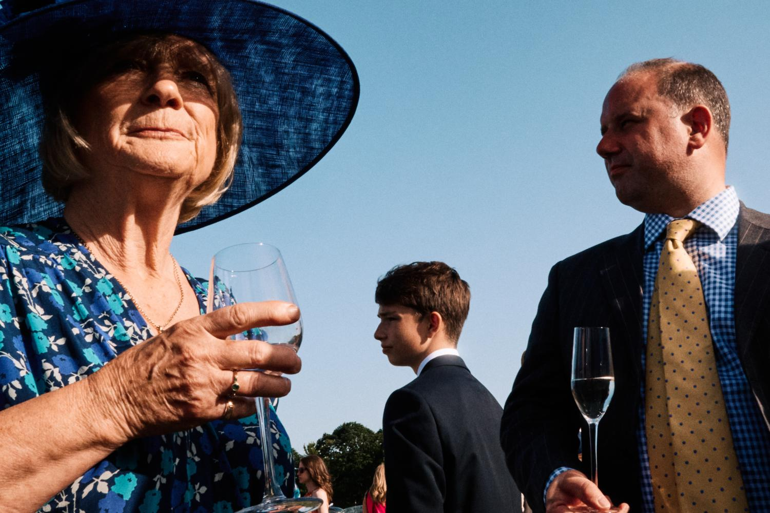 Three wedding guests look in separate directions at a wedding