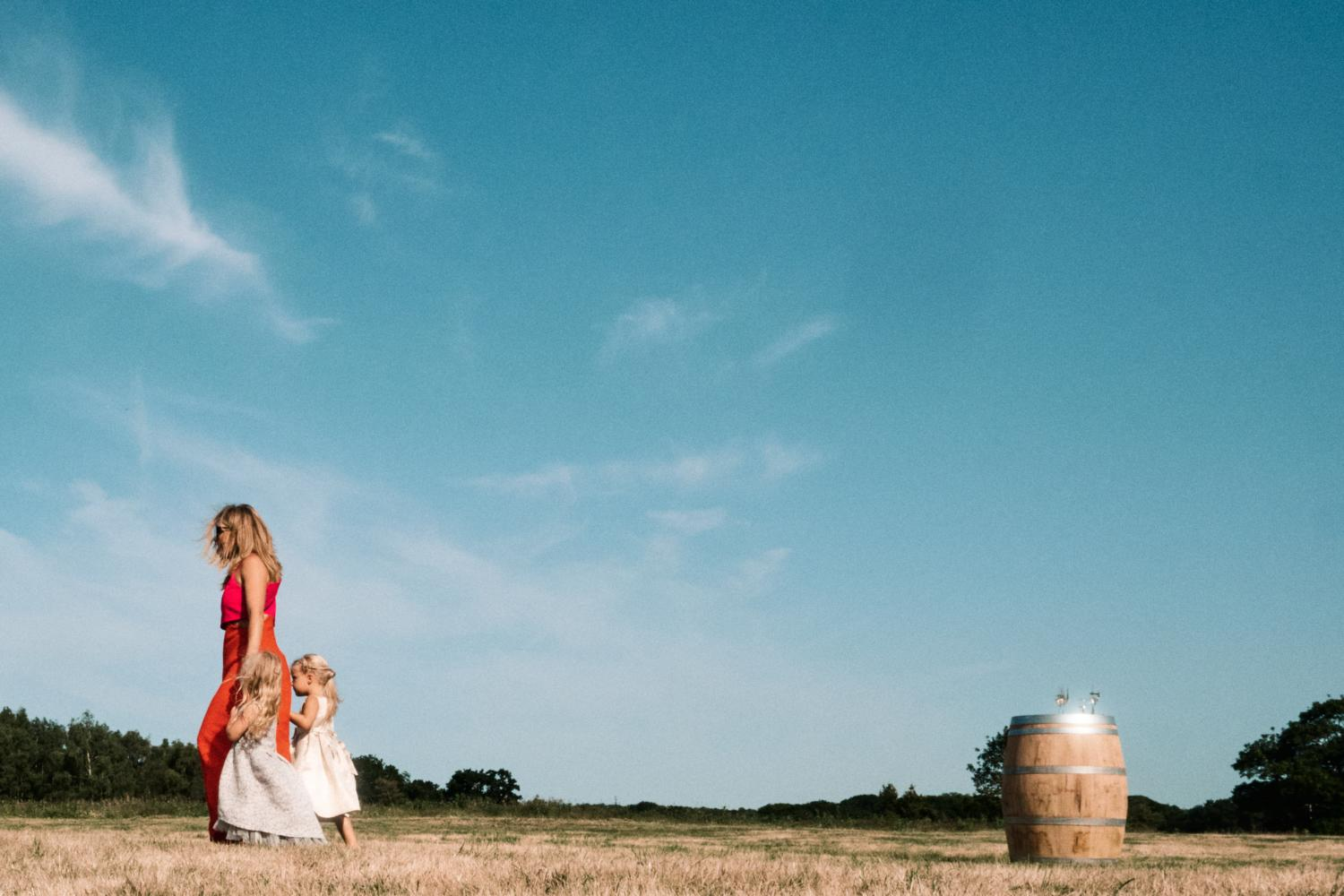 A mother walks her daughters in the opposite direction of a barrel in a field