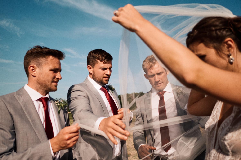 Groomsmen help the bride with her veil