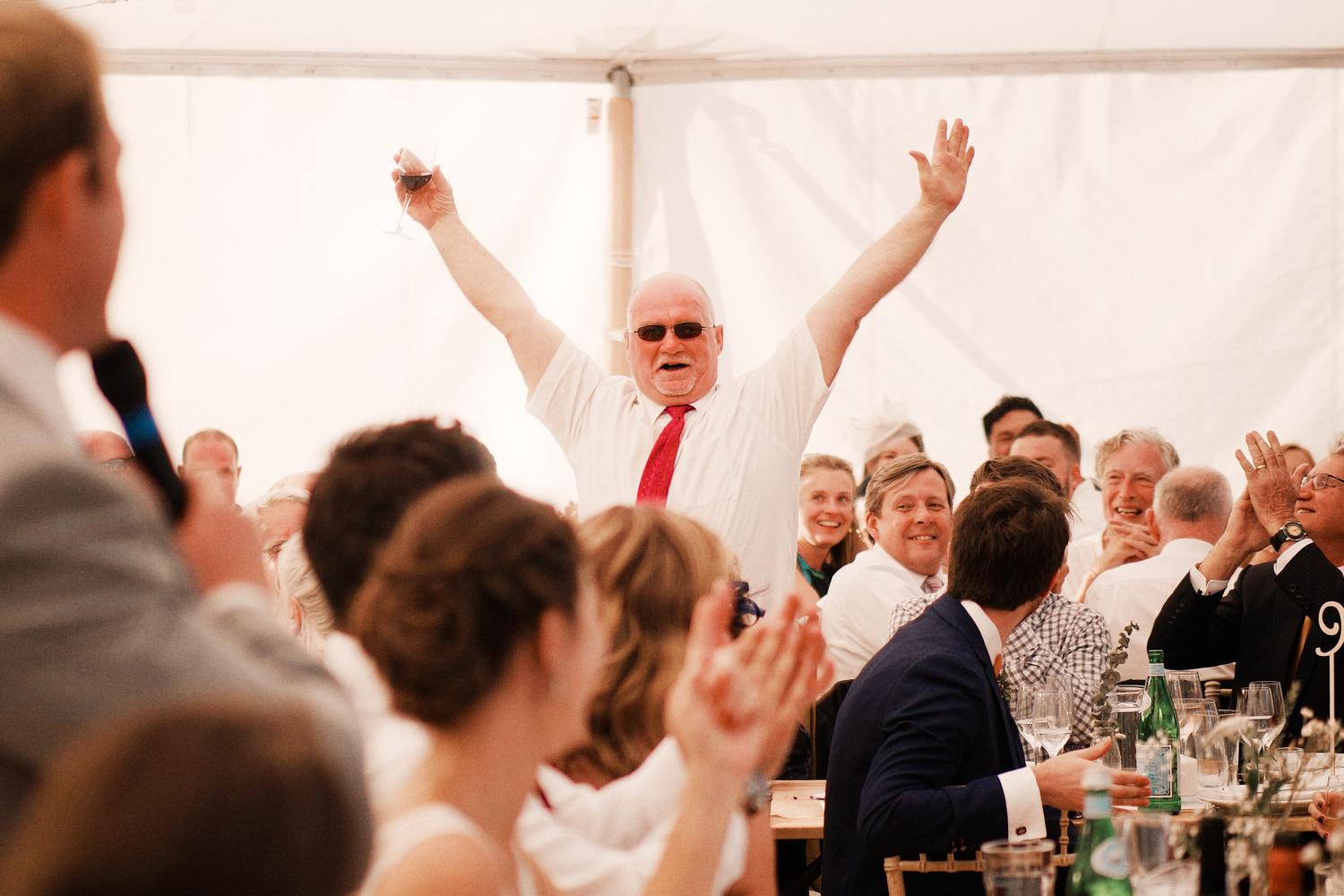 Father of the groom raises his hands dramatically during the speeches