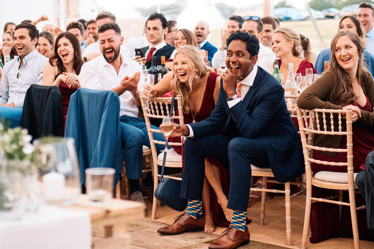 Wedding guests laughing during speeches in a marquee