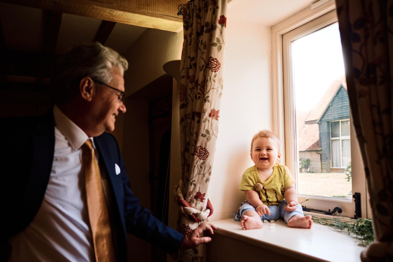 A laughing baby sits in a window frame