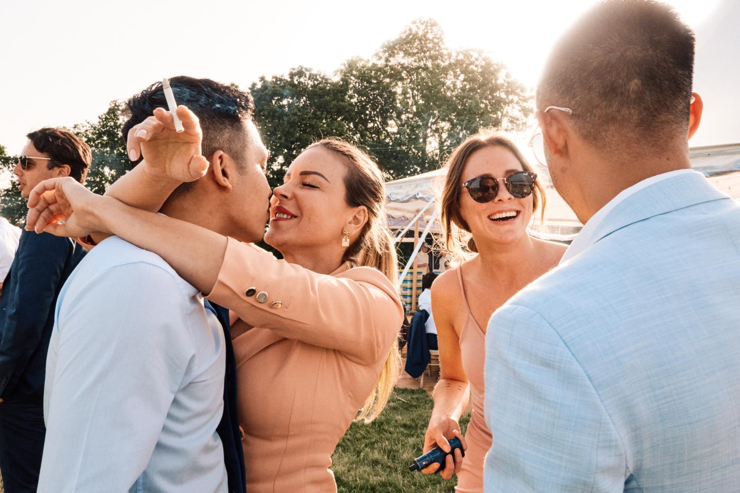 A couple kiss outside a marquee