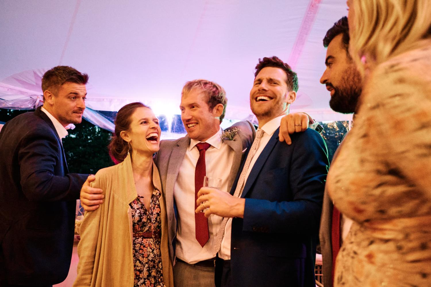 A groom holds his friends in a marquee