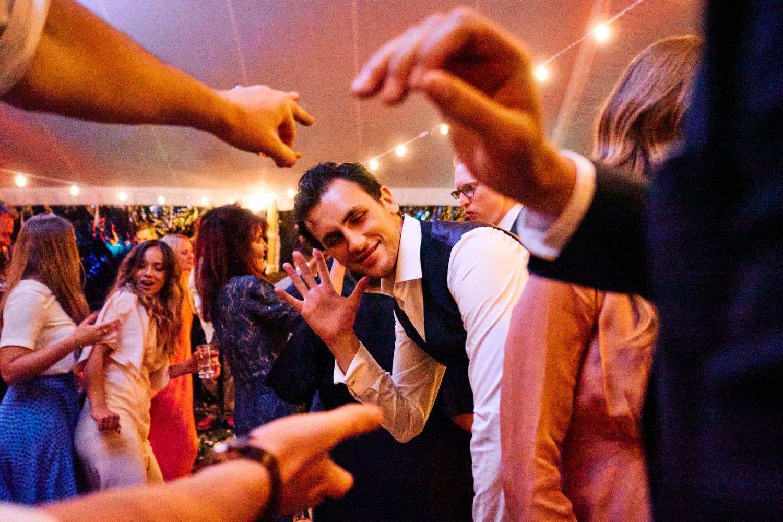 Expressive hands frame a smiling dancer on the dancefloor