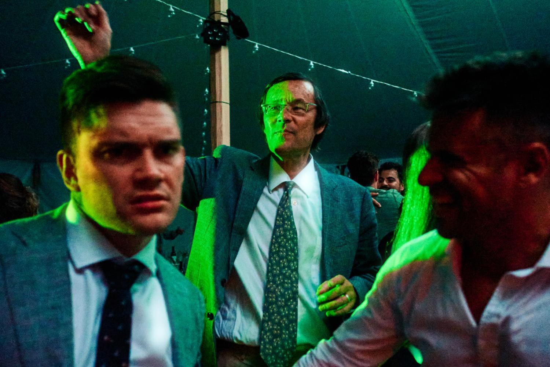 Three men dance in green light