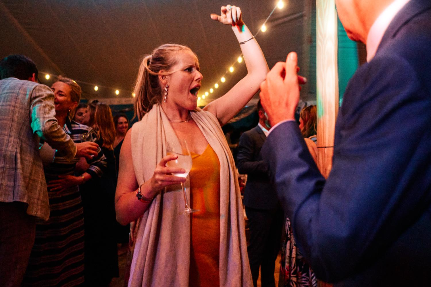 A woman gestures with her hand on the dancefloor