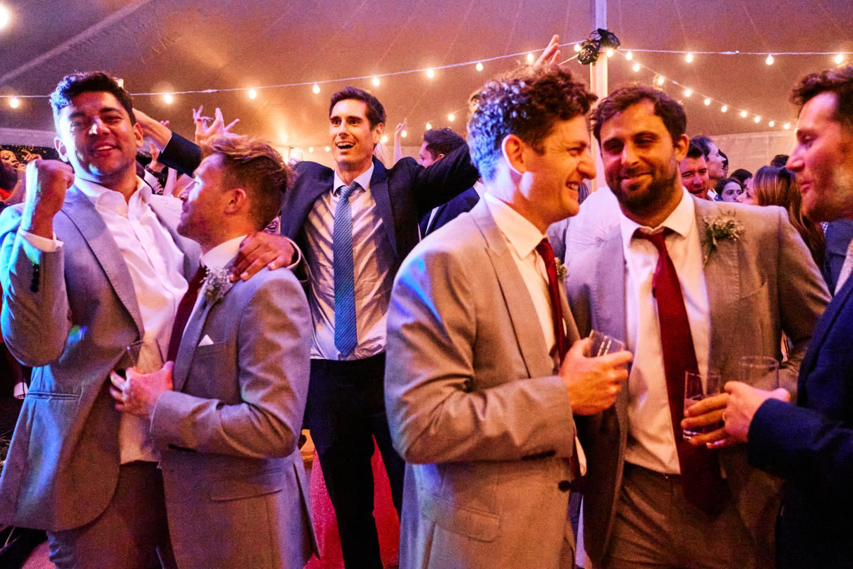 Groomsmen celebrate on dancefloor
