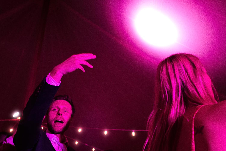 A wedding guest raises his hand on the dancefloor, in purple light