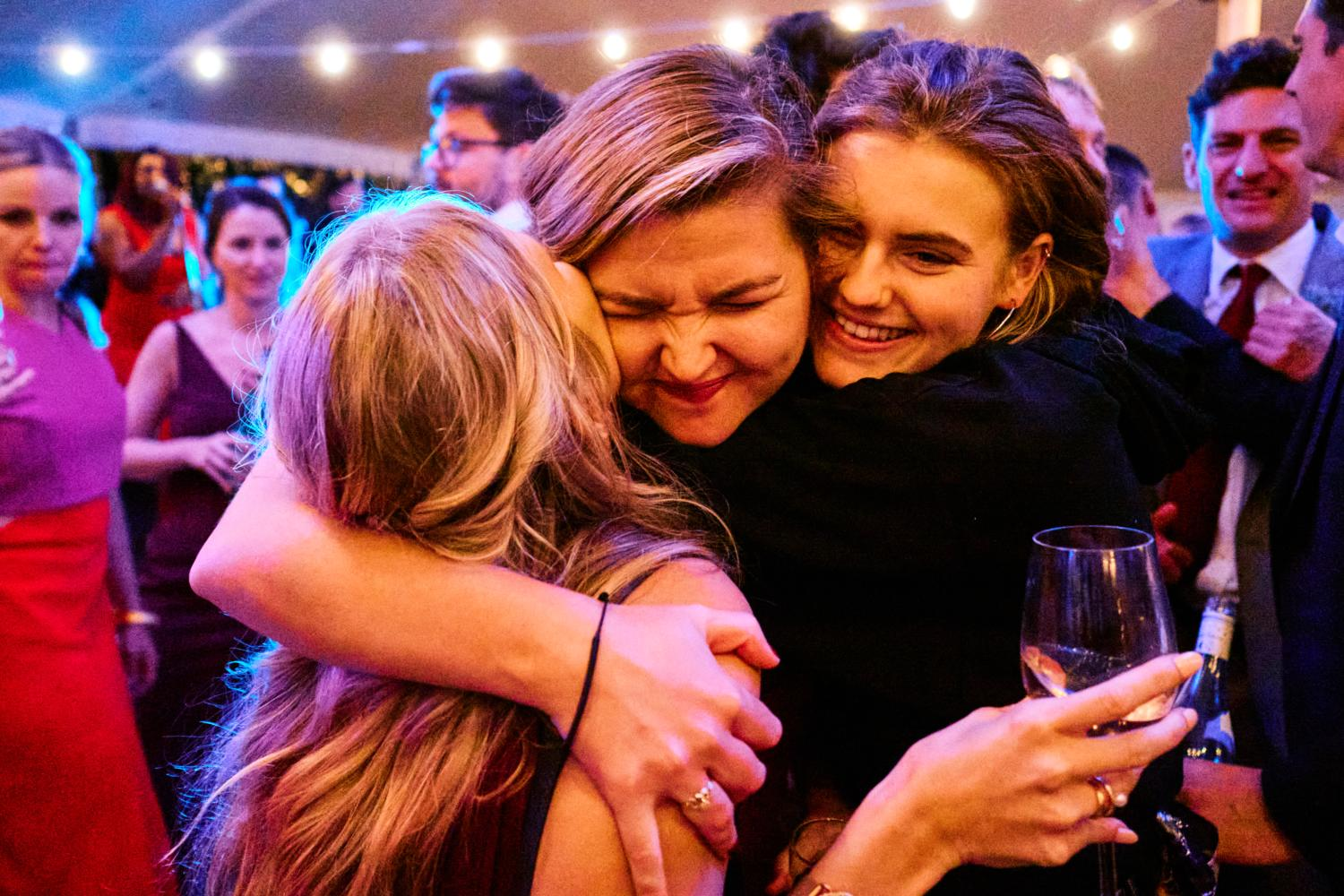 Sister of the bride hugs her friends in a marquee