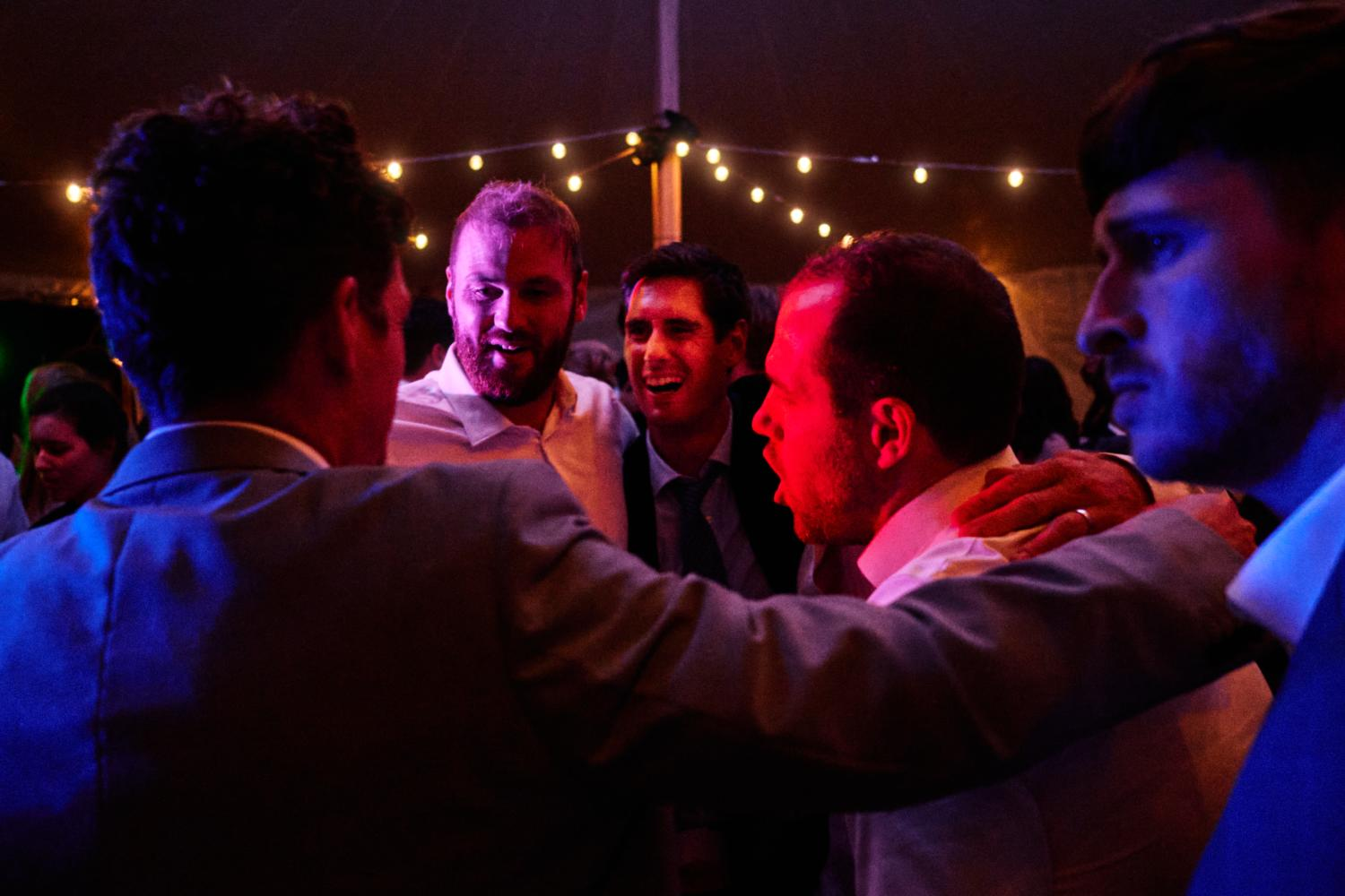 Men dance together in a marquee