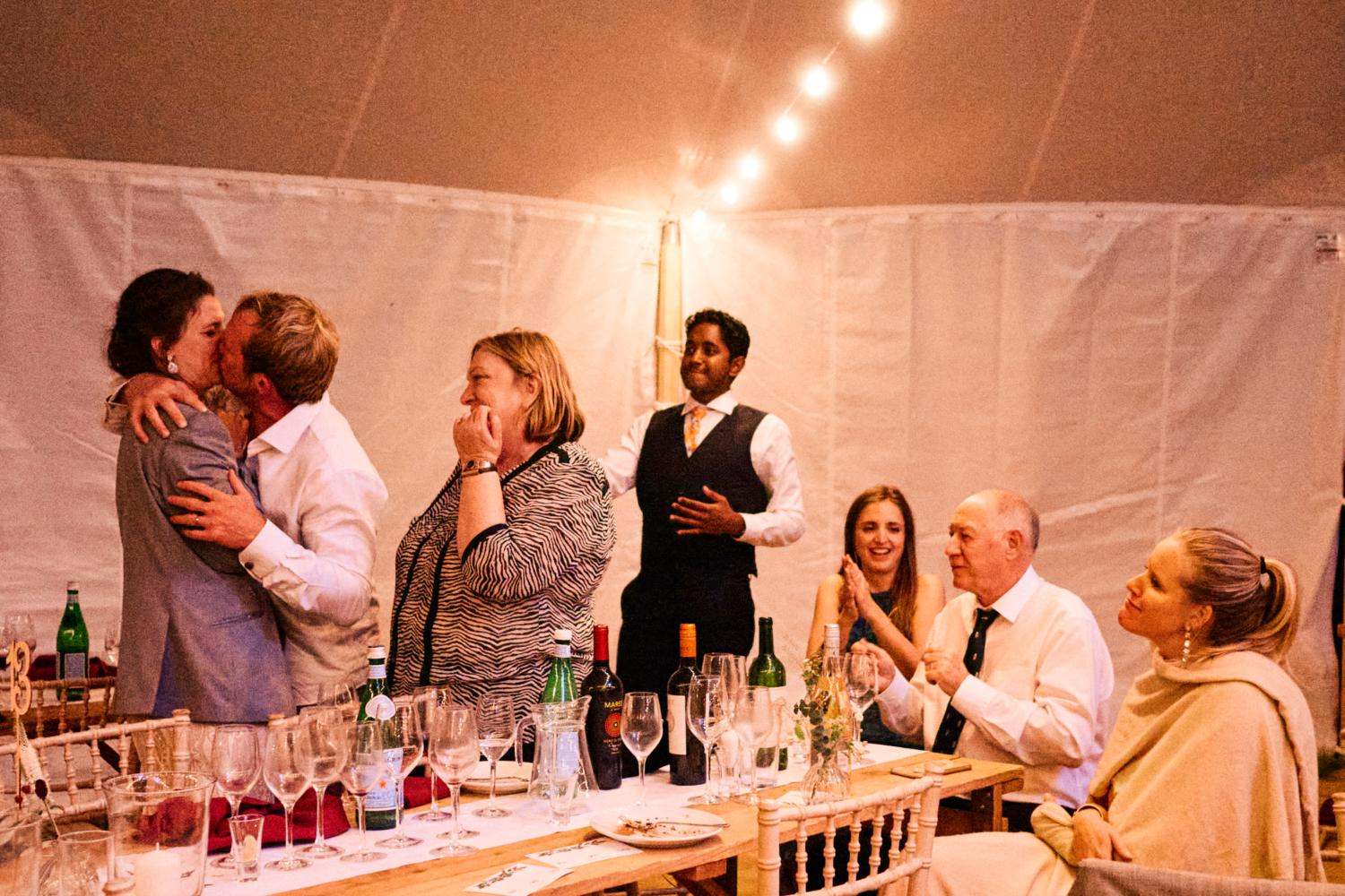 Bride and groom kiss in front of their friends in a marquee