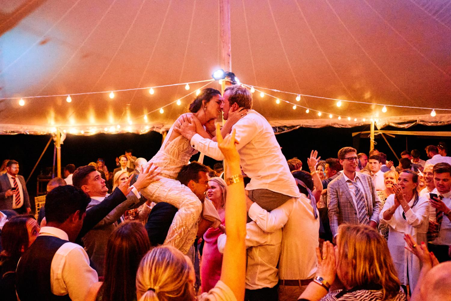 Bride and groom kiss each other on the shoulders of their friends in a marquee