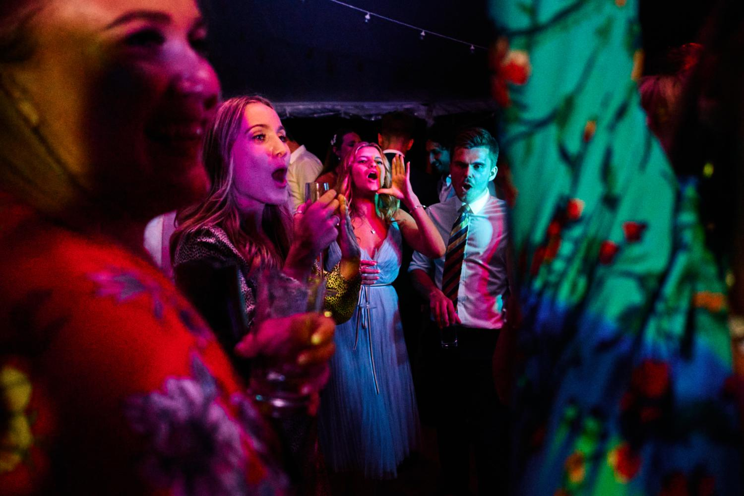 Colourful lights illuminate singing dancers at a marquee wedding reception