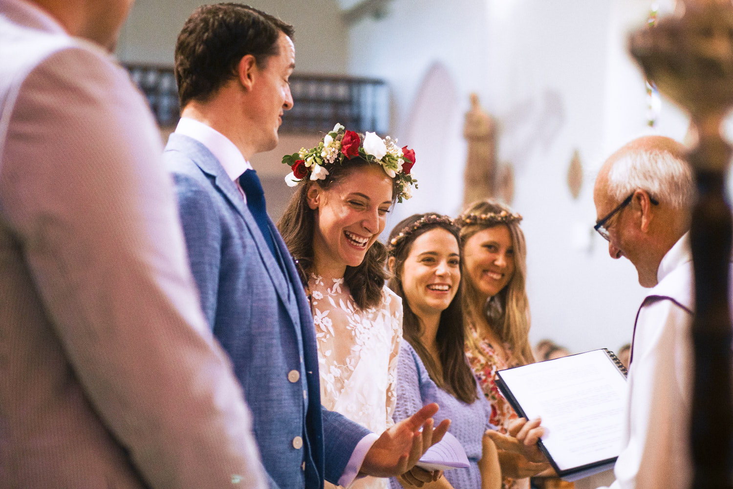 A bride and groom laugh during their vows in France