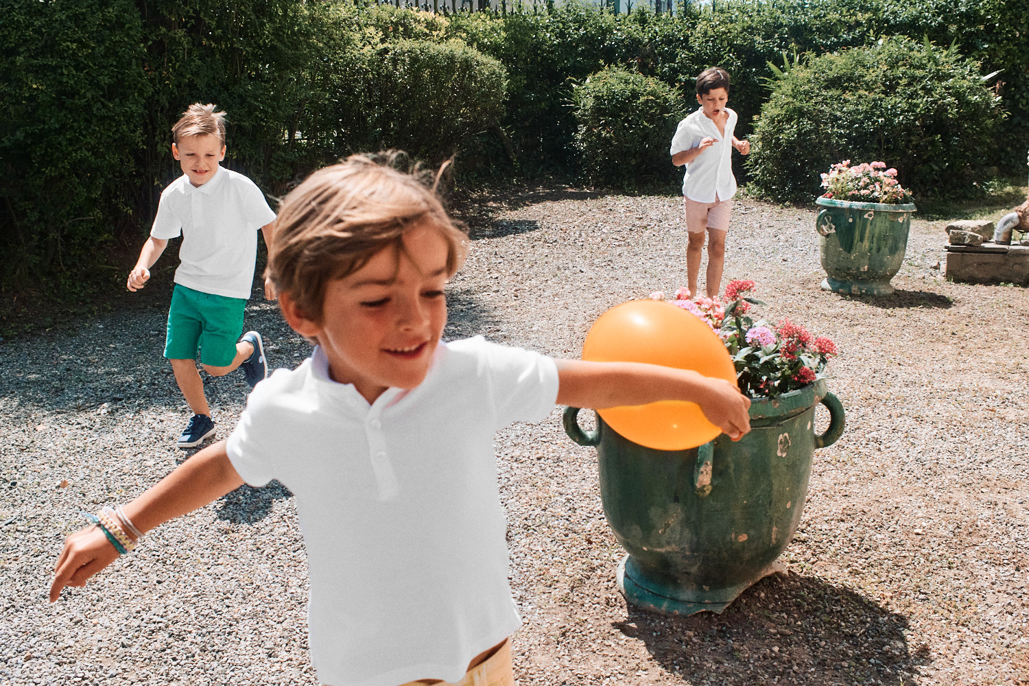 Three French children in white t-shirts play outside with orange balloon