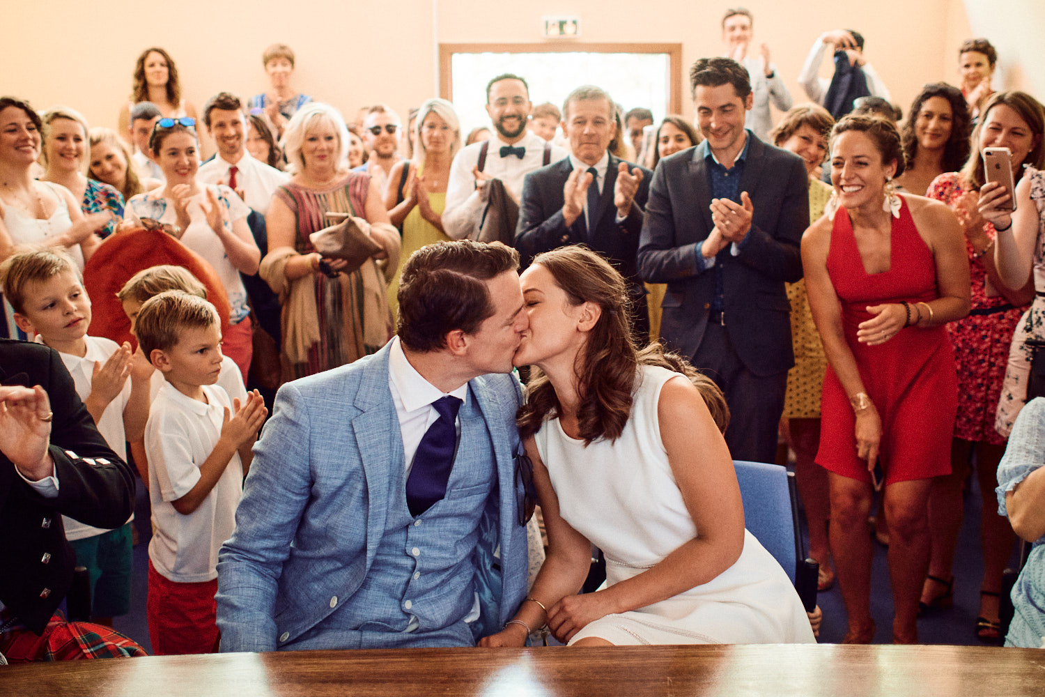 Bride and groom share a kiss as their civil ceremony concludes in French town hall