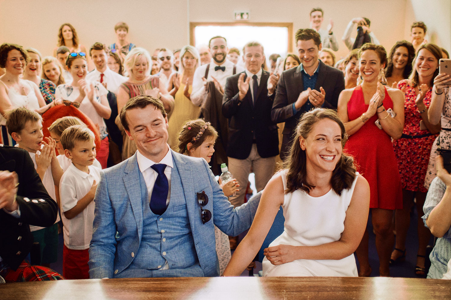 Bride and groom smile during wedding ceremony, surrounded by all their friends and family