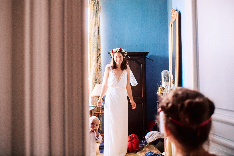 Bride in floral head piece welcomes bridal party