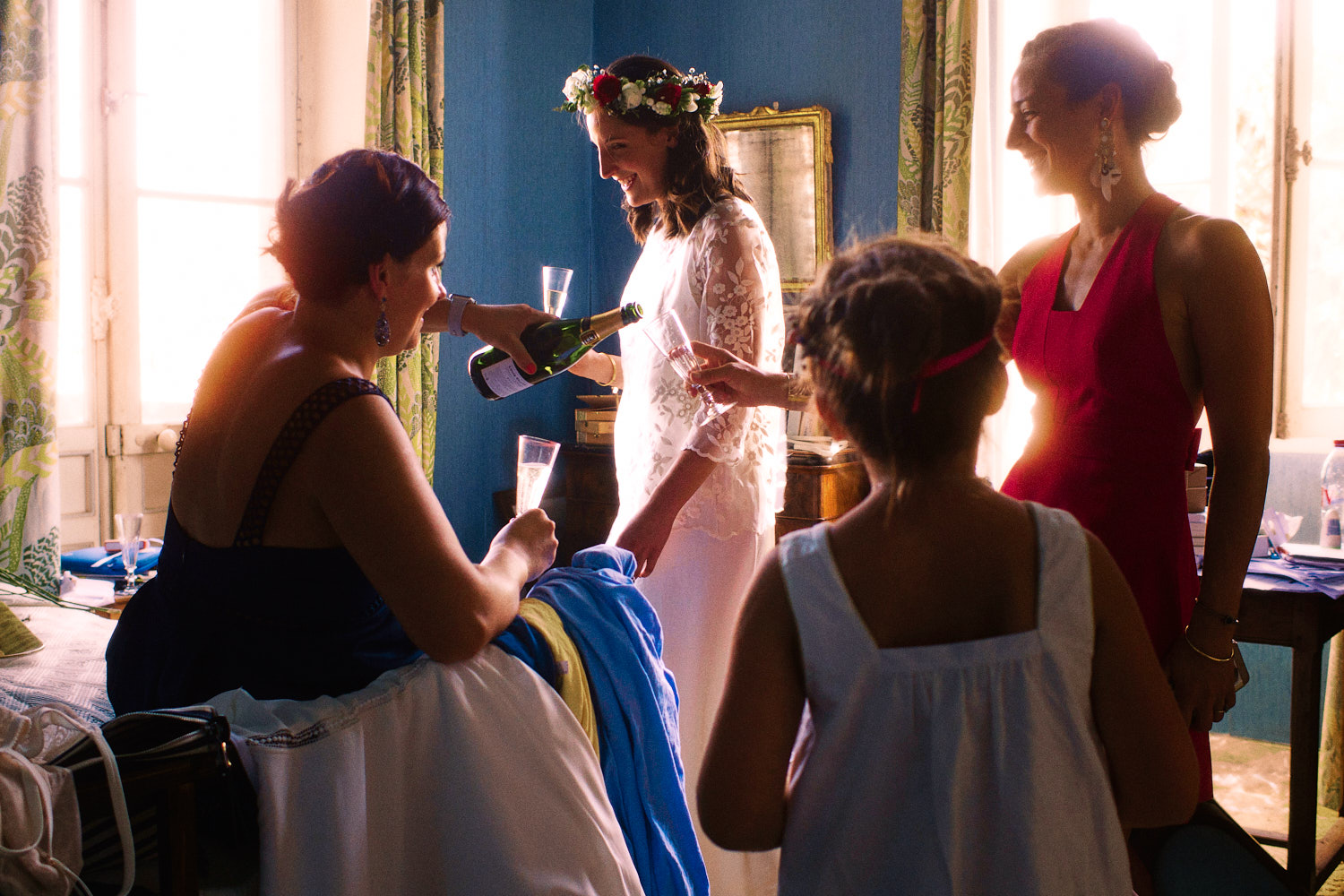 Bride in floral head piece shares champagne with her bridal party