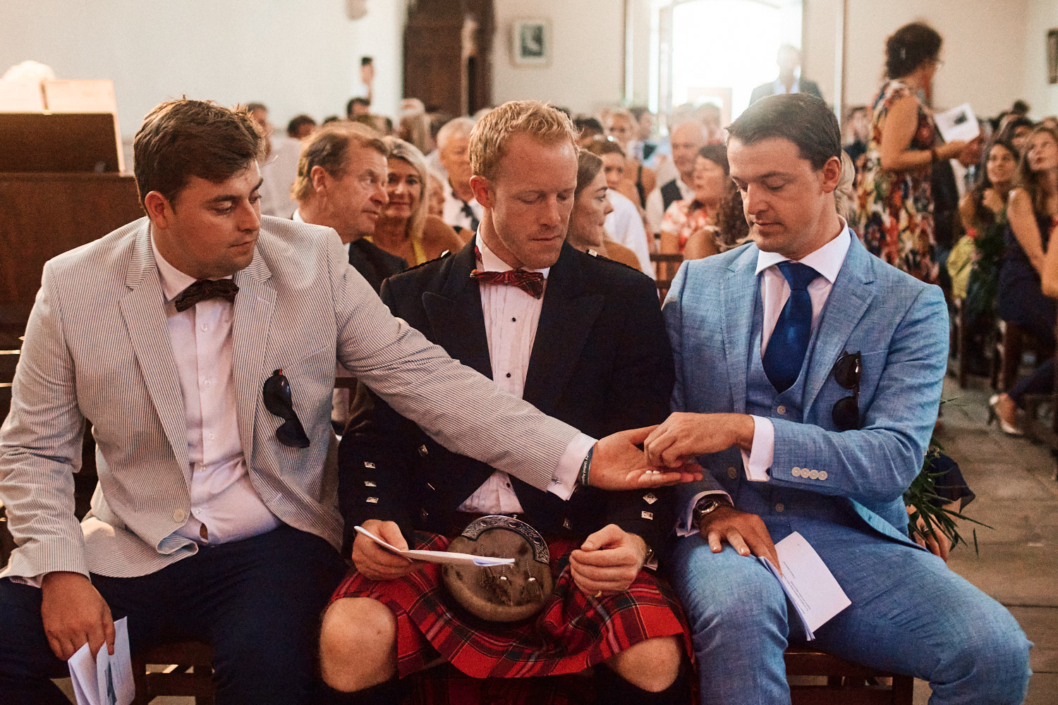 Groomsmen share chewing gum before a wedding ceremony in a French chapel