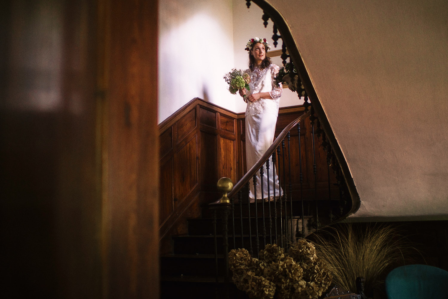 Bride walks down wooden stairs in white dress and floral head piece