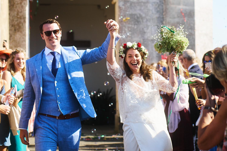 Bride and groom walk through confetti after Catholic wedding