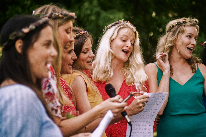 Bridesmaids sing to the bride in a garden