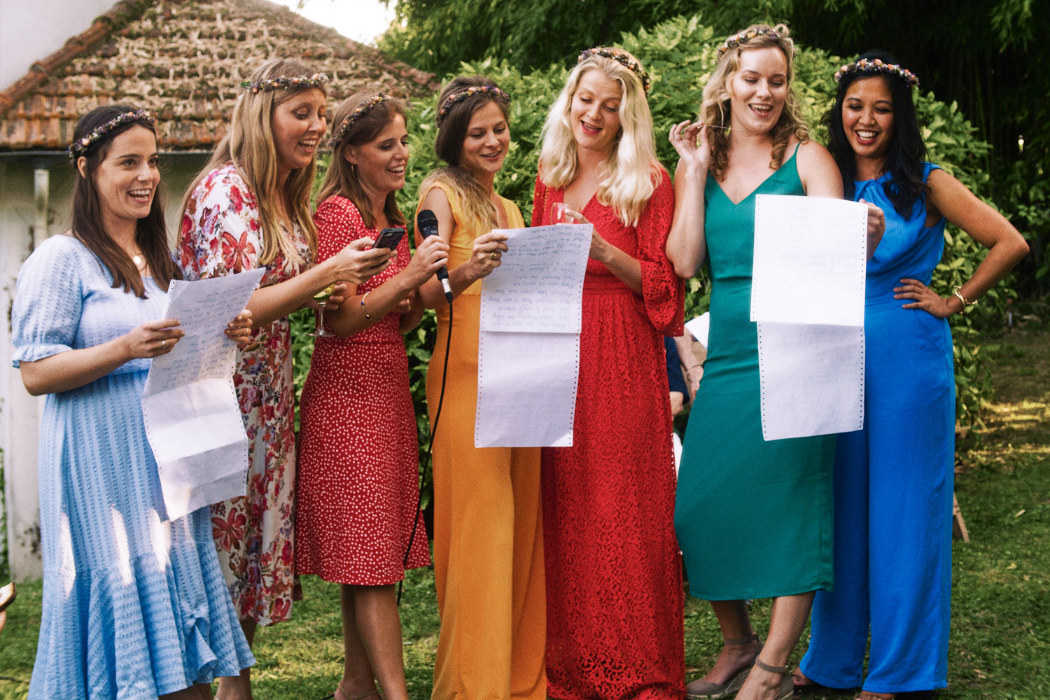Bridesmaids in colourful dresses peform speeches during garden reception