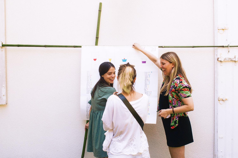 Bridesmiads erect wedding table plan on garden wall