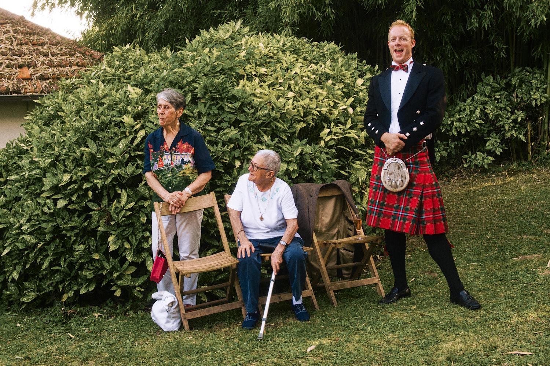 Two elderly women and a man in a kilt enjoy wedding speeches