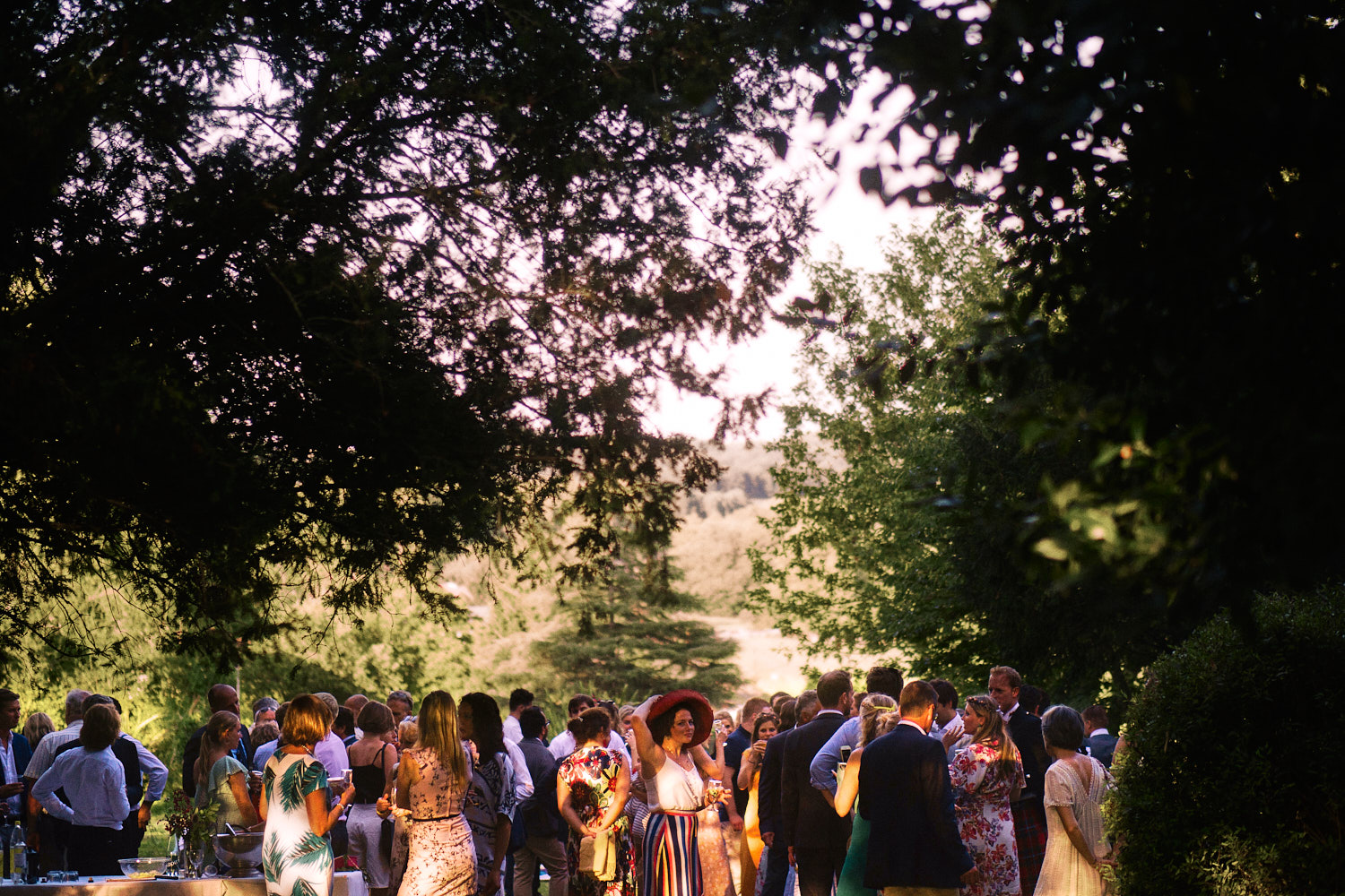 Guests mingle outside in garden during wedding ceremony